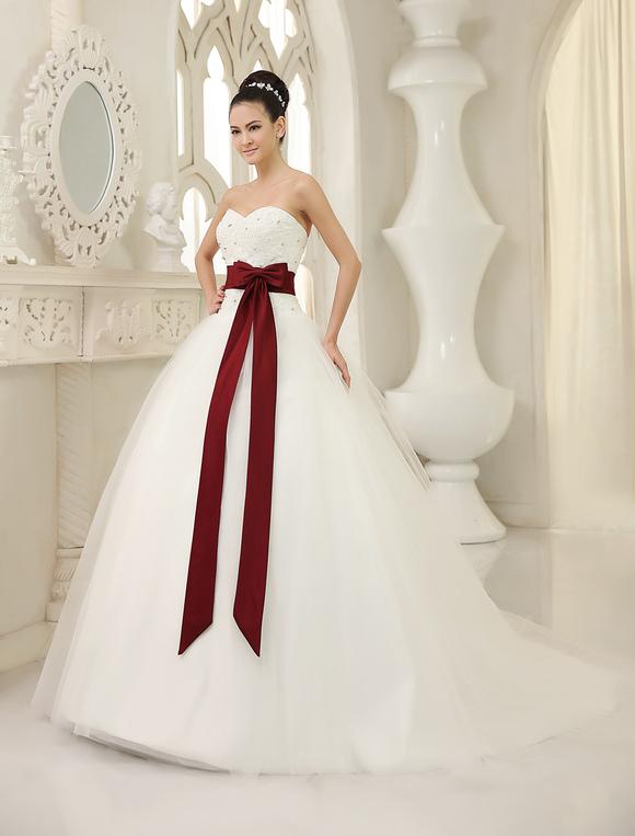 vestido de novia de tul de color marfil con lazo de cola capilla