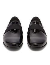 Chaussures habillées noires en cuir de vache bout rond enfilées sur les chaussures de marié